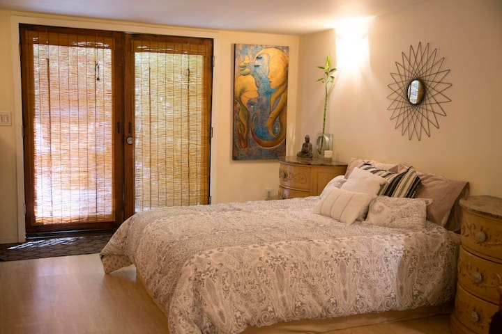 """""""Main living space with bamboo blinds and one-of-a-king original artwork from our collection"""""""
