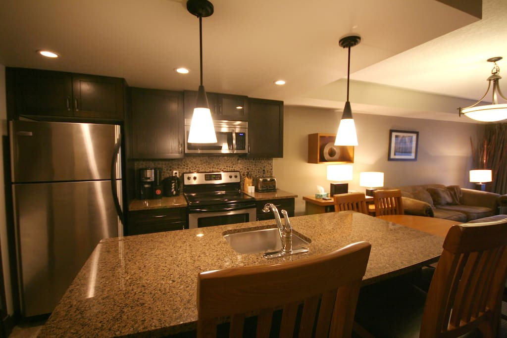 Modem full kitchen with granite countertops, stainless steel appliances, and all kinds of utensils to make your gourmet meals