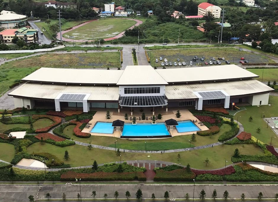 Clubhouse view from the top featuring outdoor and indoor swimming pool, basketball court, tennis court and badminton courts.