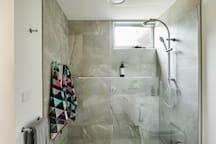 There is a large waterfall shower which is easily accessible .