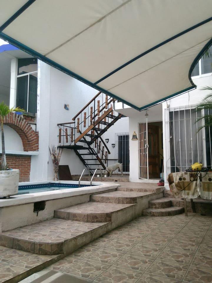en esta imagen se puede observar las escalera de subida hacia el segundo piso desde los portones de la entrada, hay un techo de lona bastante gruesa en  el patio dónde se pueden hacer asados o parrilladas.