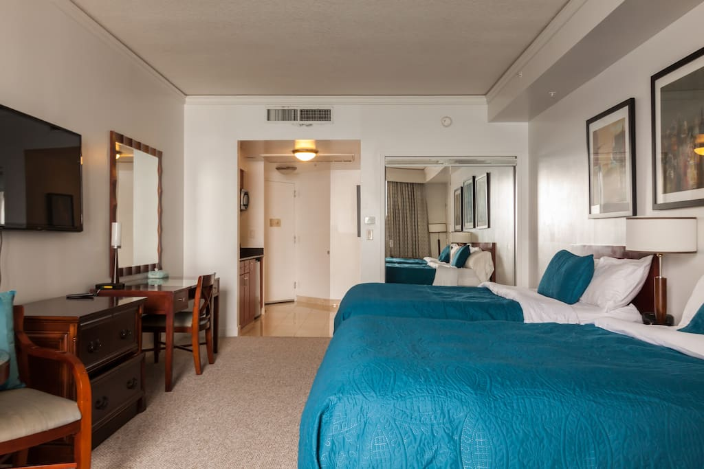 The room is furnished with 2 queen beds, a HD cable TV, a coffee table and 2 single chairs.