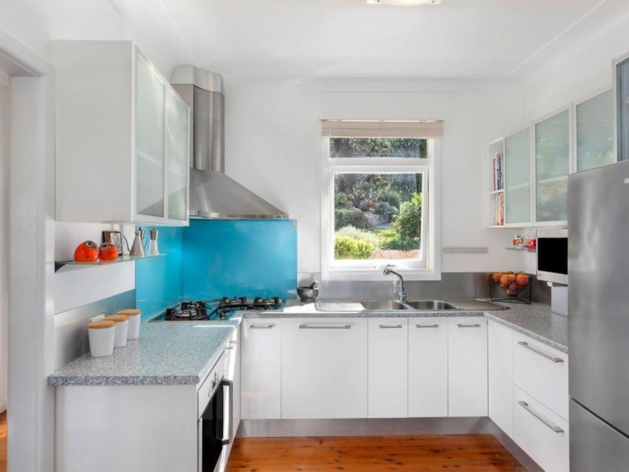 Modern kitchen with gas cooktop and views to yard.
