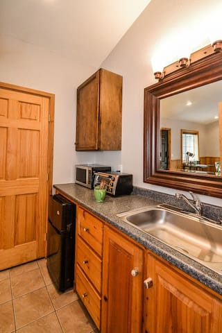 kitchenette with sink, small refrigerator, microwave, toaster oven and coffee maker