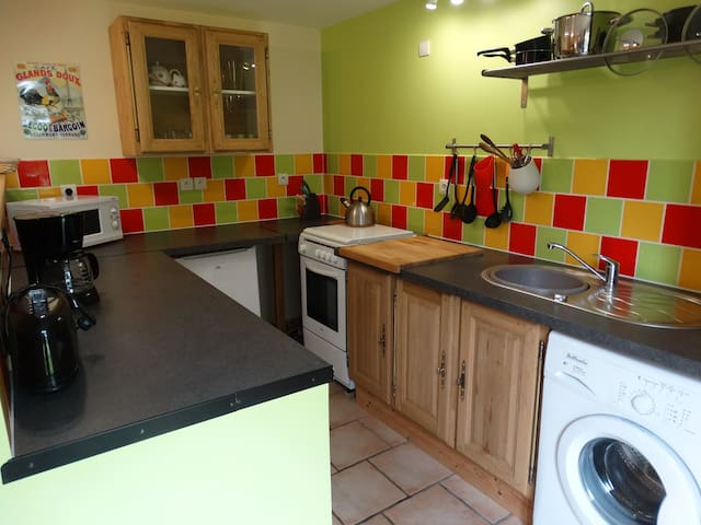 Kitchen with cooker, freezer, fridge, washing machine, coffee maker, toaster and microwave.