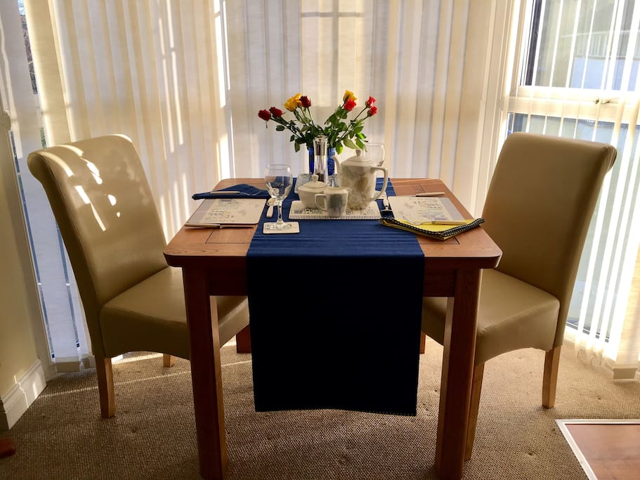 Dining area in bay window with oak table  & cream leather chairs