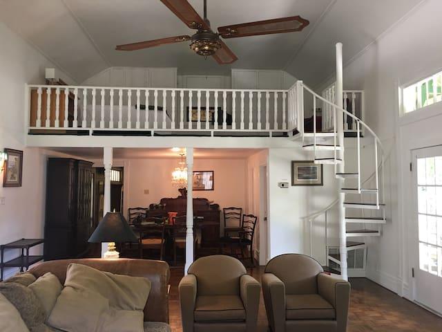 The dining area is below a bedroom loft