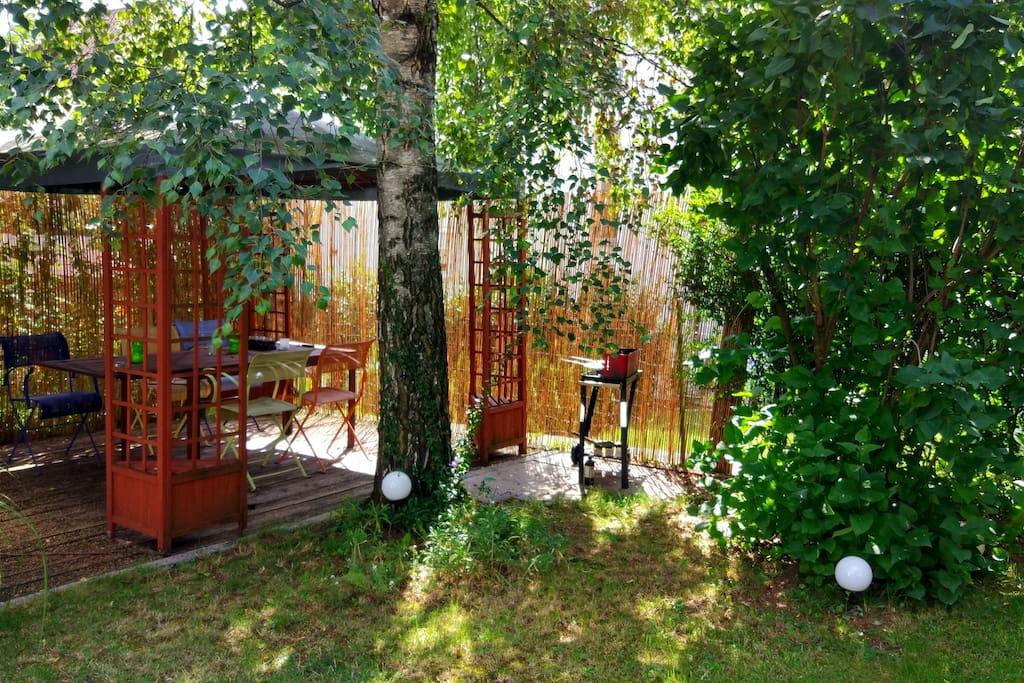 Gemütliche Grillecke unter dem Pavillon im Garten.