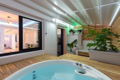 Terrasse avec toit escamotable et jacuzzi  en eau à 38 degrés, le tout est privatif .