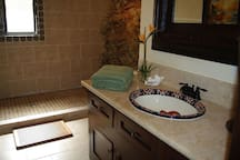 Bathroom in lower unit with natural rock wall.