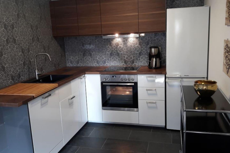 Küche mit Backofen, Ceranfeld, Kühlschrank, Tiefkühltruhe, Spülmaschine, Mikrowelle.