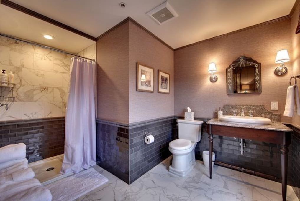 Your private bath has a beautiful and spacious, walk-in shower stall with custom tile surround.