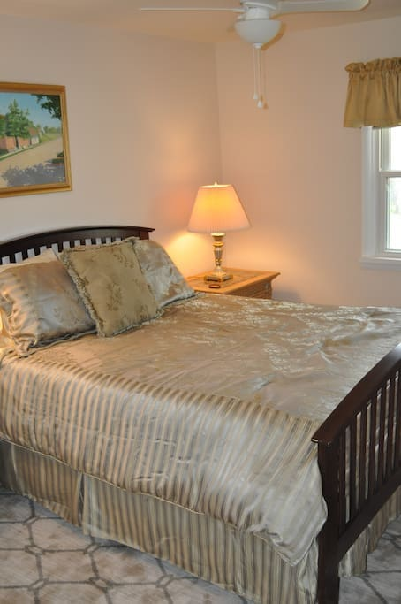 Beautiful and comfortable queen sized bed with side tables and lamps.