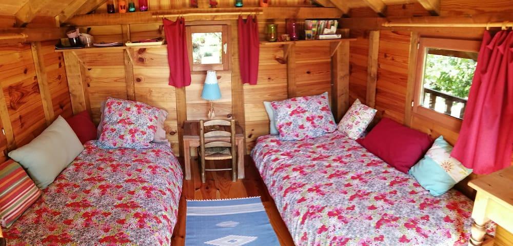 Deux lits séparés, petite commode et petite table avec cafetière et bouilloire électrique.