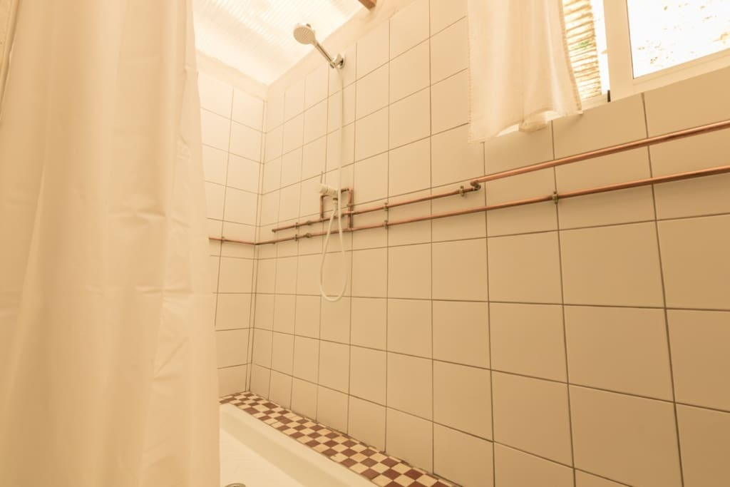 """The shower room has copper pipes decorating the walls.  When guests are using the shower they can hang their towels on the """"hot"""" pipe and the towel will warm up."""