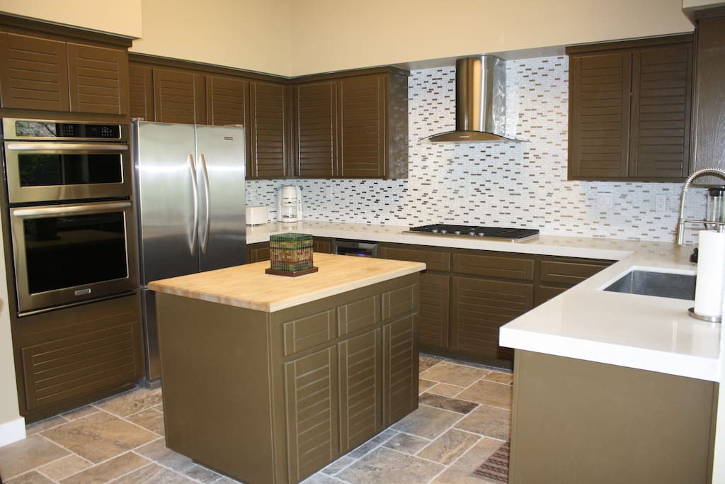 Modern kitchen with stainless steel appliances and custom tile back-splash