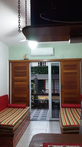 Sofás da sala que podem servir de cama para duas pessoas.  Smart TV 32' com acesso wi-fi, ar condicionado de 12 mil BTU's e ventiladores de teto.
