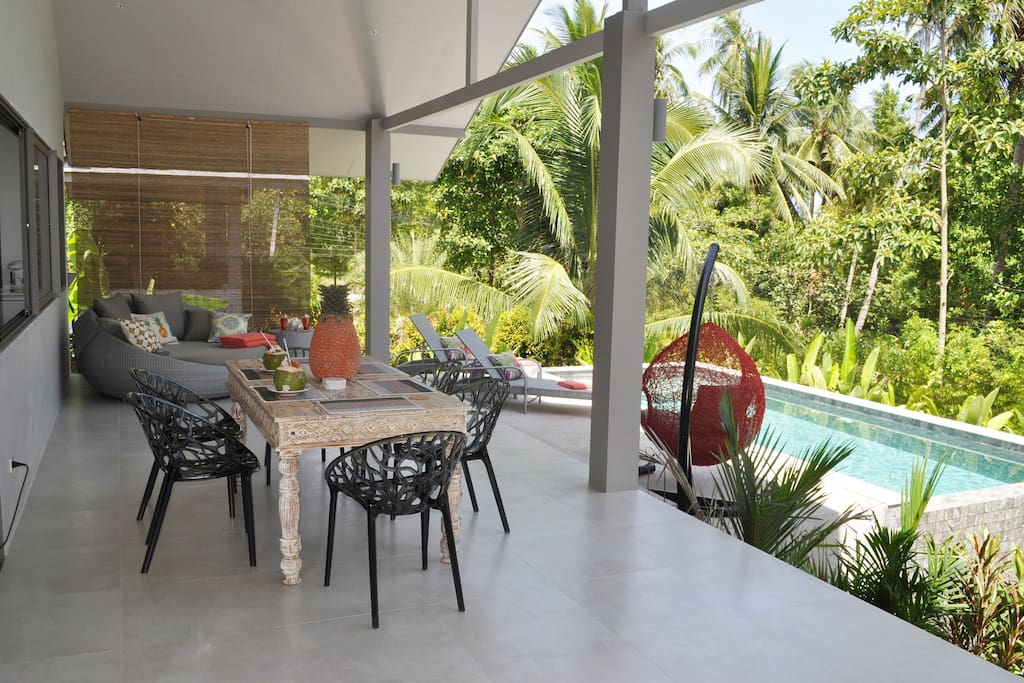 Contemporary outdoor dining on the terrace overlooking the pool