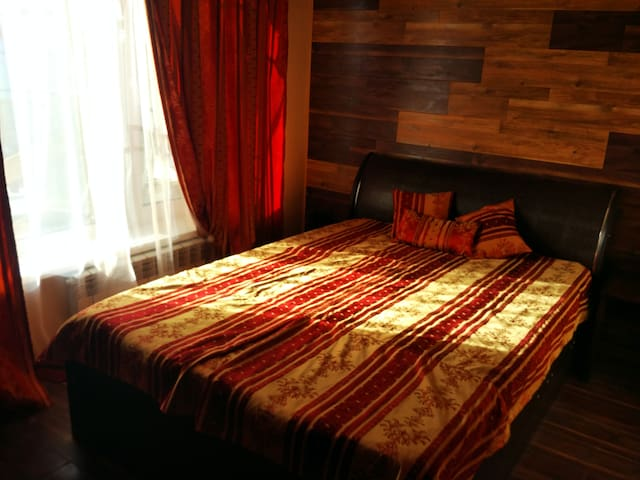 Уютная бордовая комната с двухспальной  кроватью.