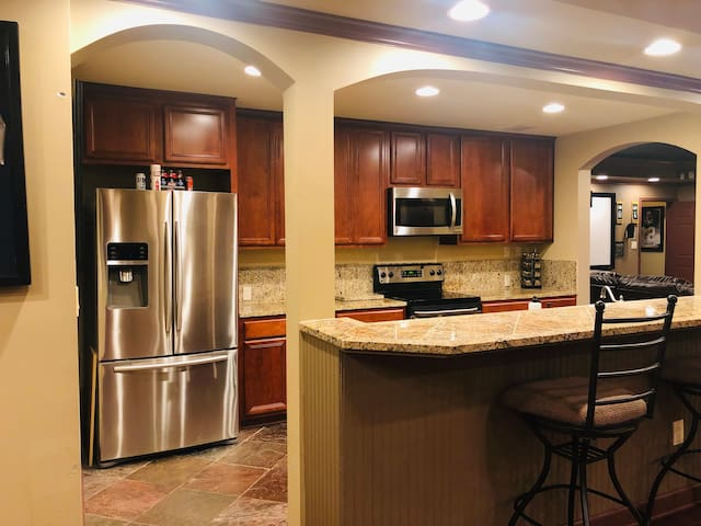 Full kitchen with stainless steel appliances, dish washer, stove, microwave and refrigerator.