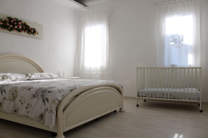 """A view of the double-bed room, with windows facing a """"calle"""". If you have infants that enjoy crying and some night desire to maximize the distance between you two, you may happily notice that the crib is wheeled."""