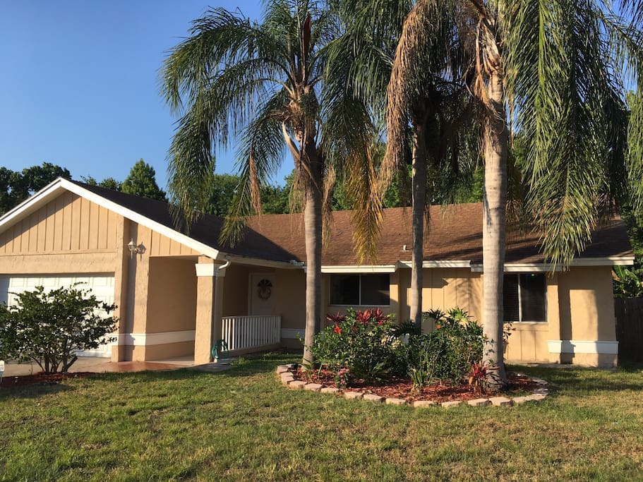 Front view of house from road, three large palm trees.