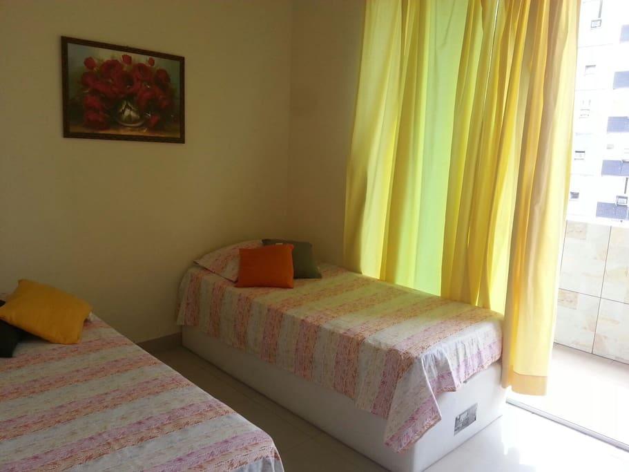 Quarto com acesso a sacada com vista para o mar, com duas camas de solteiro, espelho, ventilador de chão e wifi.