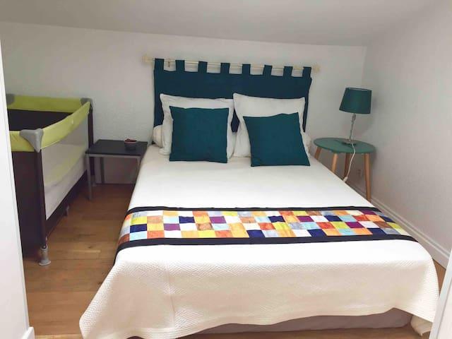 Chambre au deuxième niveau : lit parapluie, étagère, penderie