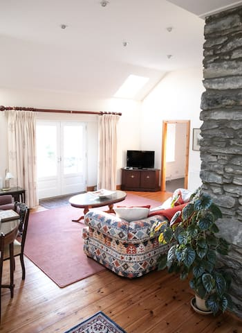 Large spacious living room with dining table.  Through the french doors you can look at the lovely country side