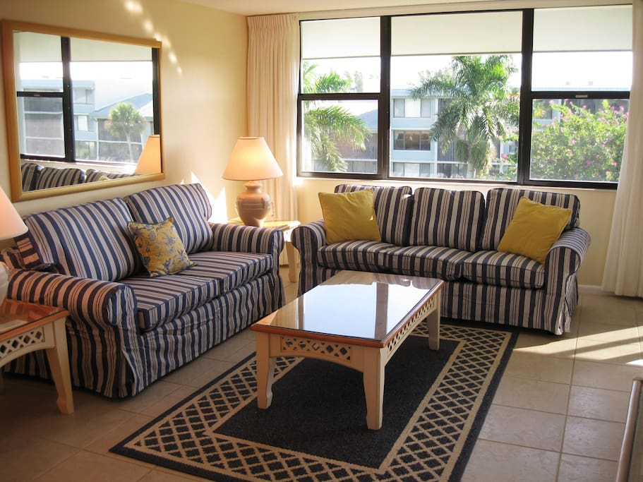 Our sunny, spacious living area features bright seating and tropical views.