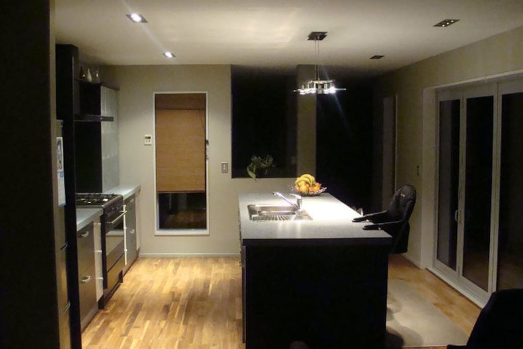 Open plan kitchen (pic taken at night), looking down towards main lounge
