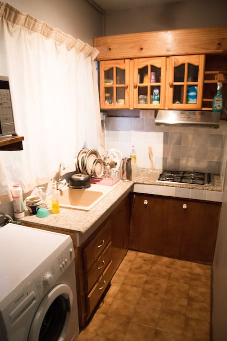 Equipped kitchen with gas stove, electric oven, microwave and a washing machine.
