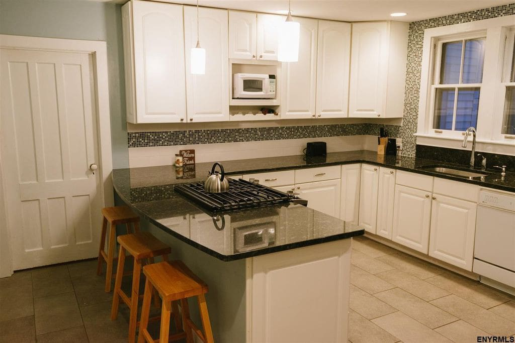 Kitchen Includes Basic Amenities: coffee maker, teakettle, tea, coffee, dinnerware, silverware, cookware, serveware, and cooking basics (olive oil, salt, pepper, basic spices, etc.)