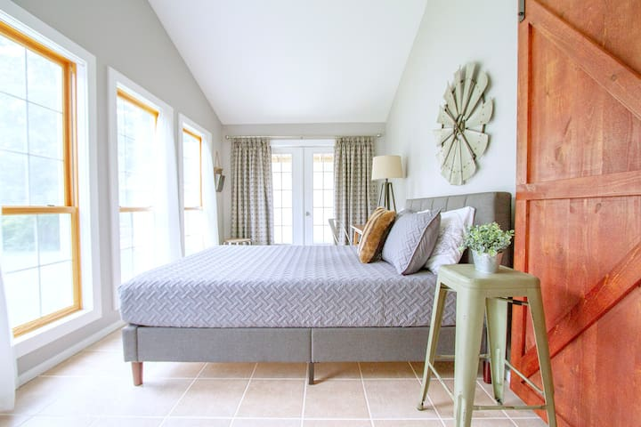 Bedroom on first floor with queen bed, large desk, and french doors leading out to private space on the wraparound porch.