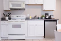 Electric stove & oven, fridge, K-Cup coffee maker, hot water kettle, toaster, microwave, dishes and utensils. Coffee, tea, water bottles, and snacks to nicely start your stay! Fire extinguisher located at the cabinet beneath the sink.