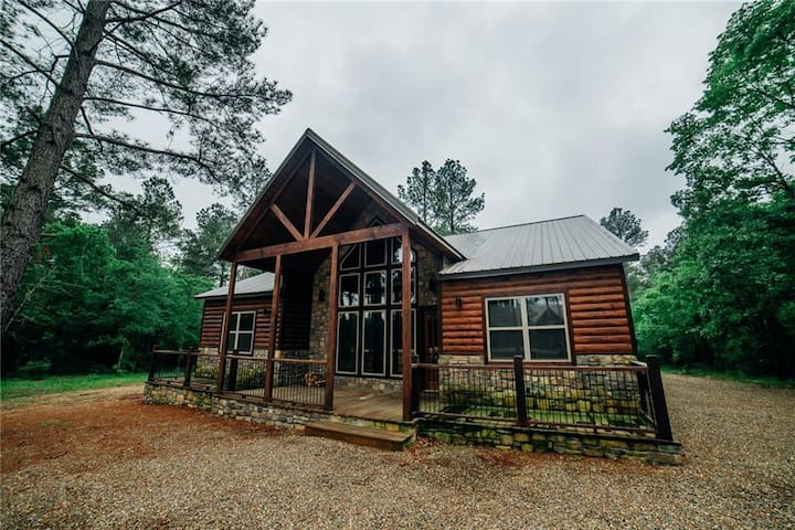 Lazy Pine Lodge This one level cabin nestled in the piney woods is the perfect getaway for family and friends to reconnect. It has 4 bedrooms with King size beds, each with its own bath.