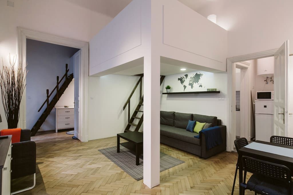 The living room and the bedroom. Two people are able to sleep on the gallery, above the couch area.