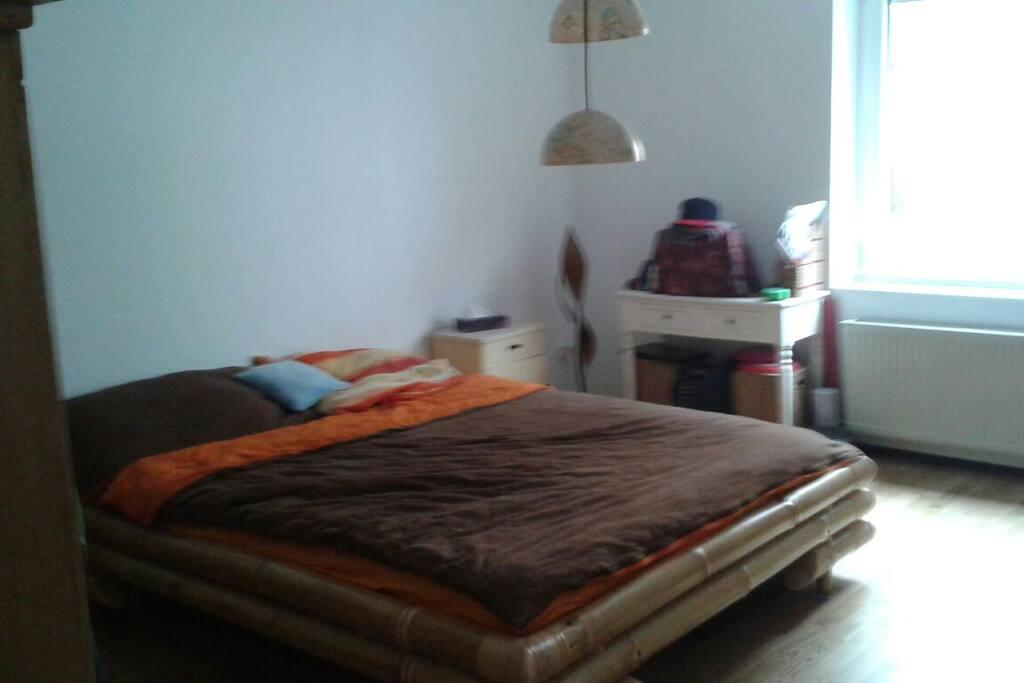 Bequemes Bett mit Fenster im Zimmer und Steckdosen.