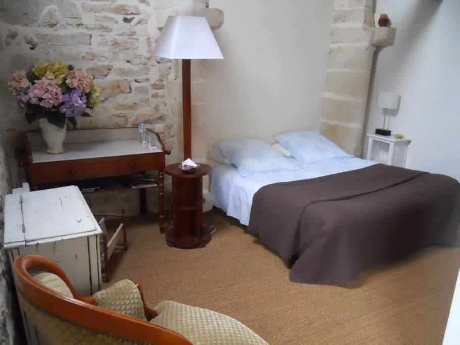 Chambre beige avec lit de 160 et sa salle de bain privée.