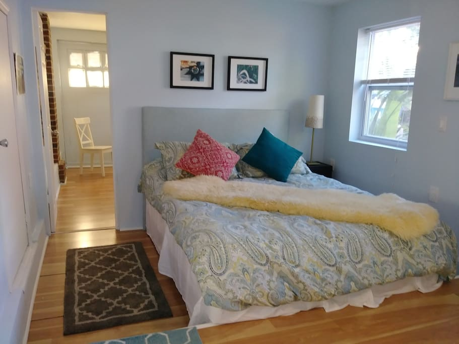 Queen bed with access to living room divided by a door.