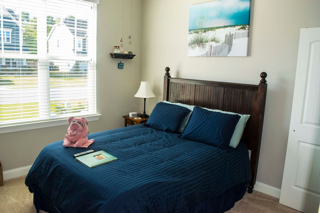 Queen-sized bed with view of the front of the house.  Your welcome binder will help you find everything you need to make your stay memorable.