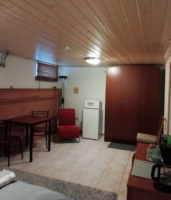 There is a fridge and microwave in the room and a small dining table and a wardrobe with additional blankets in the box.