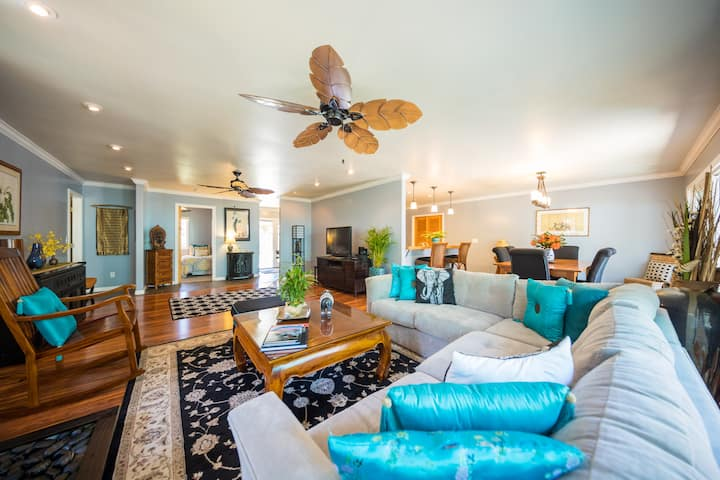 Looking for the best villas in Hawaii? This one is right next to Hawaii Volcanoes National Park! Image of a bright living room with a ceiling fan.