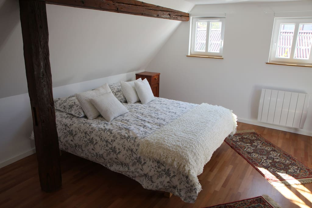 La chambre avec lit double, poutres apparentes de séparation et lit simple.