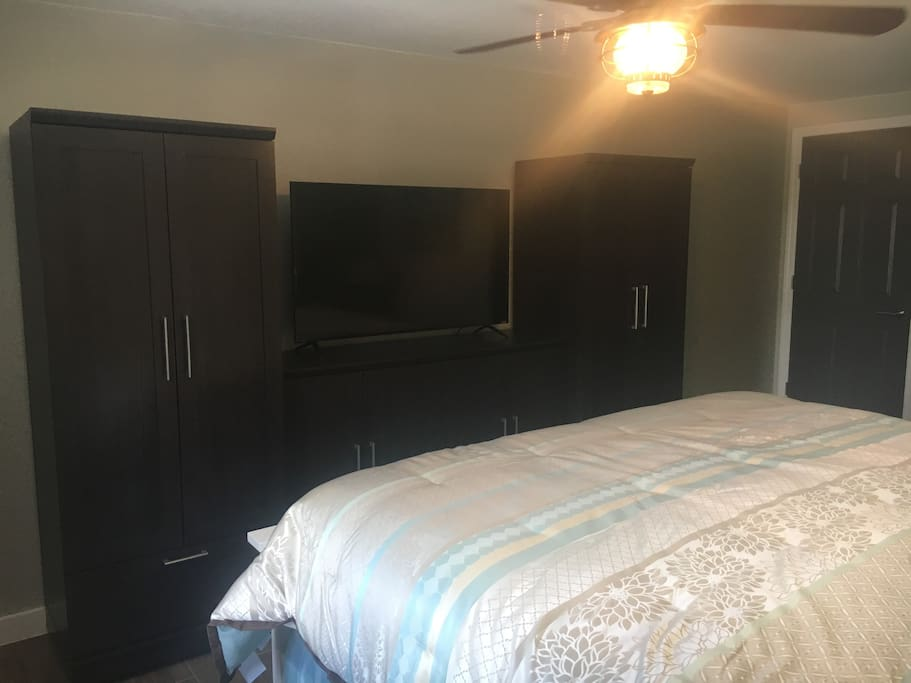 Master bedroom with large wardrobe, cabinets, smart tv, and separate bathroom only accessible through the master bedroom.