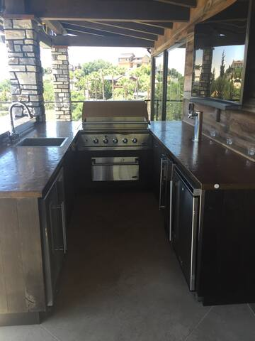 """Outdoor """"man kitchen"""" complete with gas grill, kegerator, large flat screen TV, sink and dishwasher"""