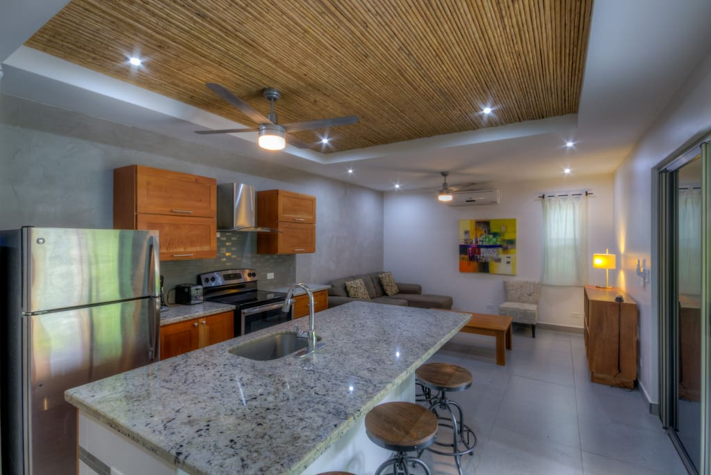 Full kitchen, large island area with seating for four people.