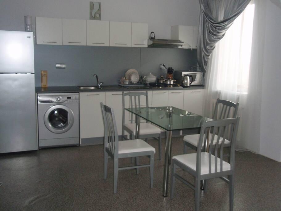 Кухня студия с холодильником, стиральной машиной, посудой, микроволновкой.