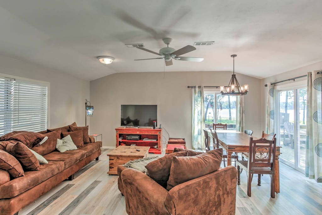 The open living space offers plush furnishings, beautiful wood floors, and views of the water.