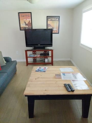 Flat screen TV and coffee table in spacious living room.